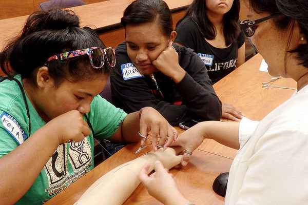 Photo shows High School and Junior High School Students learn how to stitch up wounds, using a simulated arm.