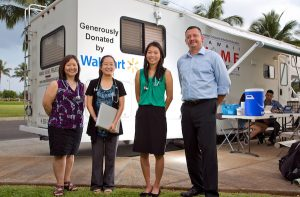 In 2014, Walmart donated a clinic/van to the HOME Project. (L to R) Dr. Jill Omori, JABSOM students Lauryn Ando and Ellyse Tom with Ray Griego, store manager for the downtown Honolulu Walmart.