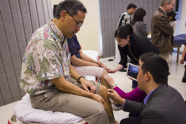 A Family Medicine Residency Program applicant examines Dr. Cedric Akau's knee as MD Residents practice locating proper sites for injection on a colleague, at JABSOM in 2014.