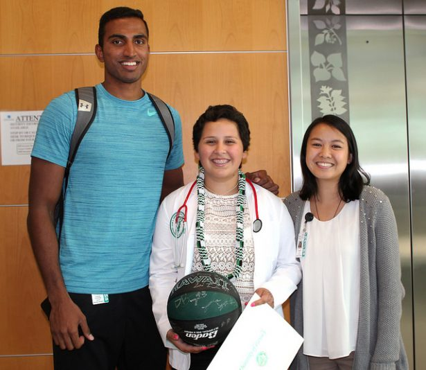 MD freshmen Sai Tummala and Carrie Ip pose with Alyssa and her student-signed UH Med basketball.