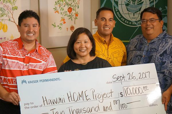 A big check is presented to Dr. Omori.