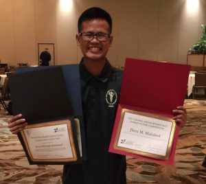 Shows Malabed holding two awards.