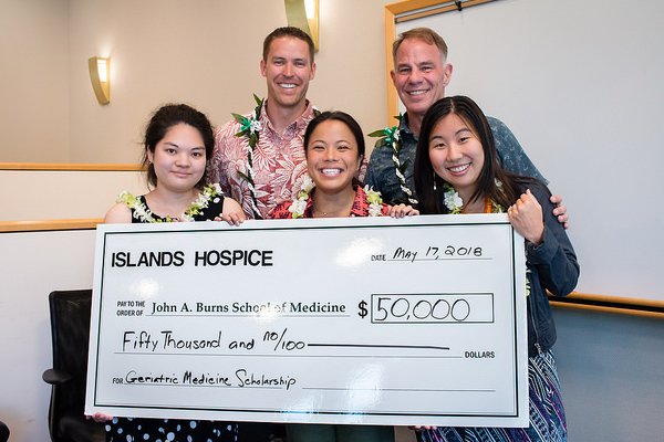 President Kevin Webb and Scott Nilsen of Islands Hospice present the $50,000 check to the MD 2019 scholarship recipients Kellie Kurasaki, Keolamau Yee and Laura Kurata.