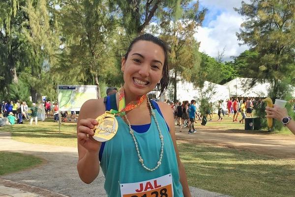 Maiya Smith after the Honolulu Marathon, holiding her finisher's medallion