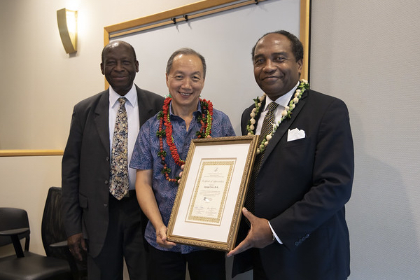 The two officials presenting a plaque to Dr. Hui