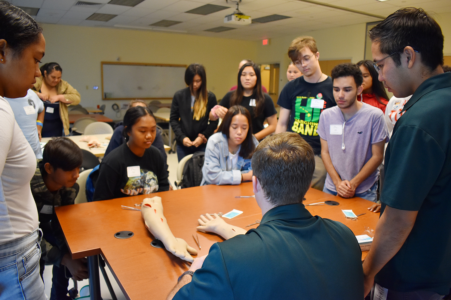 Participants learn to suture a mock arm